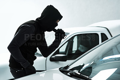 Buy stock photo Shot of a masked criminal using a torch light to look inside an empty car inside a parking lot