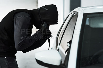 Buy stock photo Shot of a masked criminal using a steel weapon to break inside a car