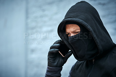 Buy stock photo Shot of a male burglar taking a phone call outdoors