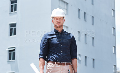 Buy stock photo Shot of a mature male construction worker holding blueprints while standing outside a building