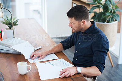 Buy stock photo Cropped shot of a handsome mature businessman looking through some paperwork while sitting in his office