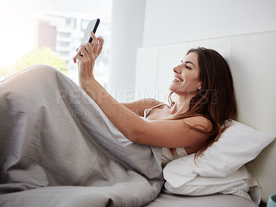 Buy stock photo Shot of a beautiful young woman talking selfies while lying in bed
