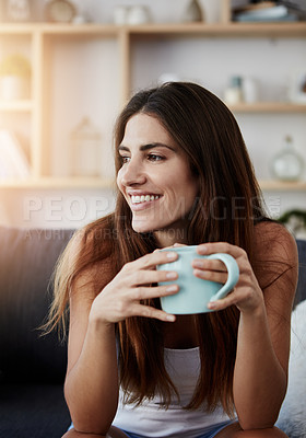 Buy stock photo Shot of a young woman enjoying a cup of coffee while relaxing in the lounge