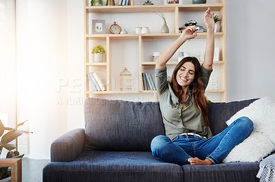 Buy stock photo Shot of a happy young woman dancing while sitting on her sofa at home