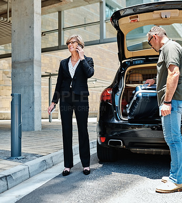 Buy stock photo Shot of a mature businesswoman talking on a cellphone while a driver carries her suitcase at an airport