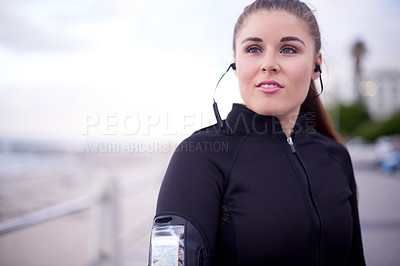 Buy stock photo Cropped shot of an attractive young woman looking thoughtful while out for a run on the promenade