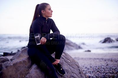 Buy stock photo Cropped shot of an attractive young woman looking thoughtful while taking a break from her workout on the beach