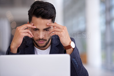 Buy stock photo Shot of a young businessman using a laptop in a modern office and looking stressed