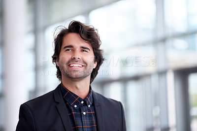 Buy stock photo Shot of a confident young businessman walking through a modern office