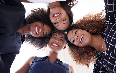 Buy stock photo Low angle portrait of a group of young businesswomen huddling in a modern office
