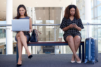 Buy stock photo Full length shot of two attractive young businesswoman sitting on a bench in an airport departure lounge