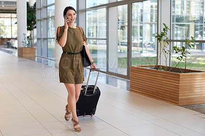 Buy stock photo Full length shot of an attractive young businesswoman making a phonecall while walking through an airport terminal