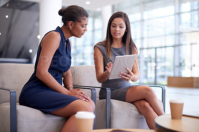 Buy stock photo Cropped shot of two attractive young businesswoman looking at a tablet while sitting in their office