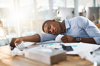 Buy stock photo Shot of a young businessman suffering with a cold while sitting at his desk