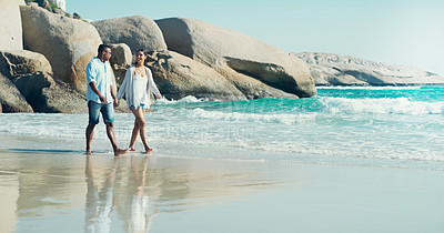 Buy stock photo Full length shot of a happy young couple taking a walk by the seashore