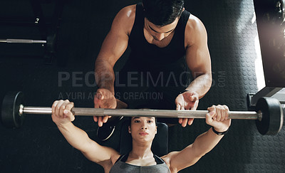 Buy stock photo Shot of a young woman lifting weights with her personal trainer assisting her
