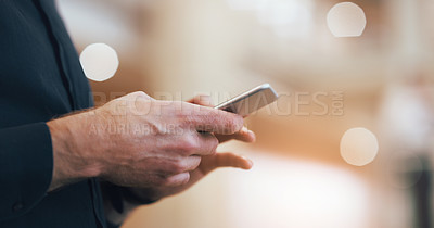 Buy stock photo Cropped shot of an unrecognizable businessman using a mobile phone in a modern office
