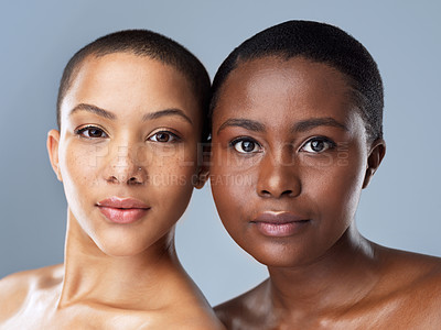 Buy stock photo Portrait of two beautiful young women standing close  to each other against a grey background