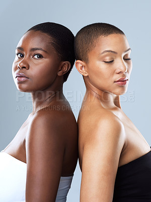 Buy stock photo Portrait of two beautiful women standing back to back against a grey background