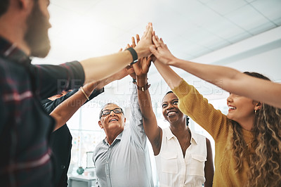 Buy stock photo Cropped shot of a group of designers high fiving during a meeting in the boardroom