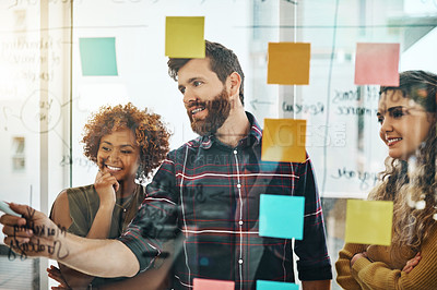 Buy stock photo Cropped shot of three designers working together on a glass wipe board in their office
