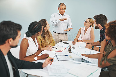 Buy stock photo Cropped shot of a handsome mature businessman addressing his staff during a meeting in the boardroom