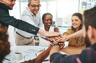 Buy stock photo Cropped shot of a group of designers with their hands in a huddle during a meeting in the boardroom