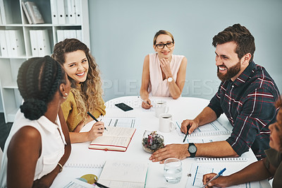 Buy stock photo Cropped shot of a group of young designers sitting in the boardroom during a meeting