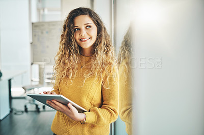 Buy stock photo Cropped shot of an attractive young female designer looking thoughtful while using her tablet in the office