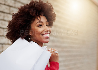 Buy stock photo Cropped shot of a young woman carrying shopping bags while out in the city