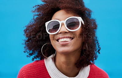 Buy stock photo Cropped shot of a young woman wearing sunglasses against a blue background