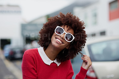 Buy stock photo Cropped shot of a fashionable young woman wearing sunglasses while out in the city