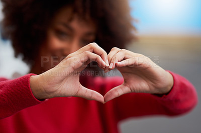 Buy stock photo Cropped shot of an unrecognizable woman forming a heart shape with her fingers