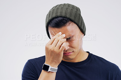 Buy stock photo Shot of a young man holding his head while suffering from a headache against a grey background
