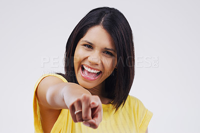 Buy stock photo Portrait of a beautiful young woman pointing to the camera against a grey background