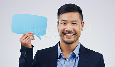 Buy stock photo Portrait of a handsome young businessman holding a speech bubble against a grey background