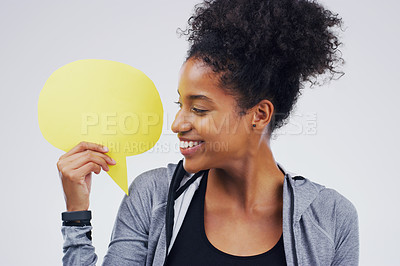 Buy stock photo Shot of an attractive young woman holding speech bubble against a grey background