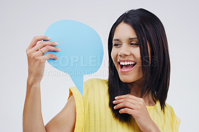 Buy stock photo Shot of an attractive young woman looking surprised while holding a speech bubble against a grey background