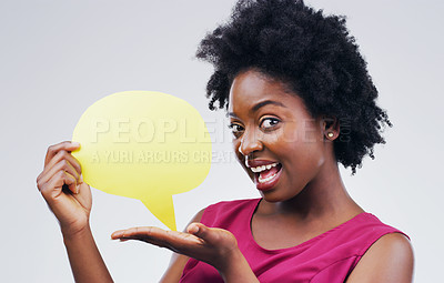 Buy stock photo Portrait of an attractive young woman looking surprised while holding a speech bubble against a grey background