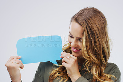Buy stock photo Shot of an attractive young woman holding speech bubble against a gre