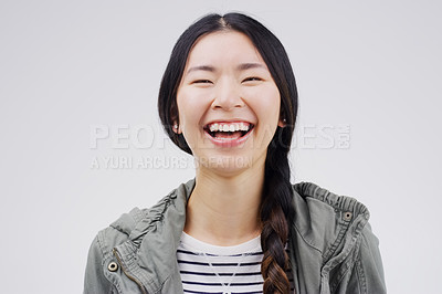 Buy stock photo Studio portrait of an attractive young woman laughing while standing against a grey background