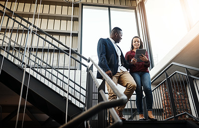Buy stock photo Low angle of two colleagues having a quick meeting with a tablet on the staircase