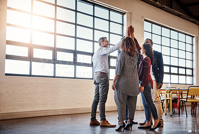 Buy stock photo Full length of a diverse team of happy businesspeople high fiving each other in the office
