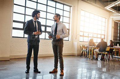 Buy stock photo Full length of two well-dressed businessmen brainstorming together over a tablet in their office