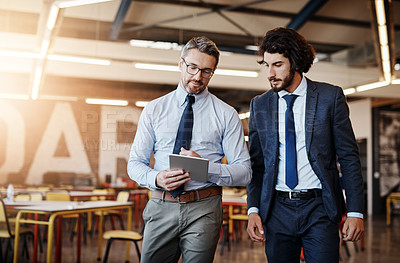 Buy stock photo Cropped shot of two well-dressed businessmen brainstorming together over a tablet in their office