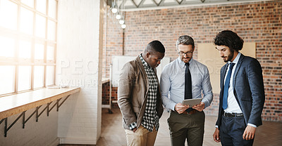 Buy stock photo Cropped shot of three well-dressed businessmen brainstorming together over a tablet in their office