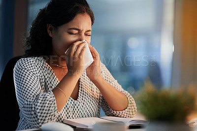 Buy stock photo Shot of a young businesswoman blowing her nose while working in an office at night