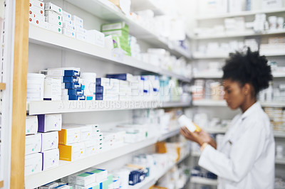 Buy stock photo Defocused shot of medication on shelves with a pharmacist in the background