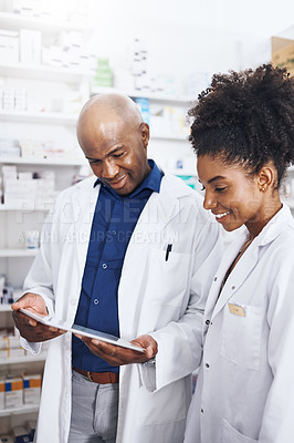 Buy stock photo Shot of two pharmacists doing inventory in a pharmacy with a digital tablet