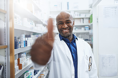 Buy stock photo Shot of a confident pharmacist showing thumbs up in a chemist